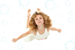 Girl Child Swimming. Beautiful 7 year old girl in white dress swimming over white with blue bubbles royalty free stock image