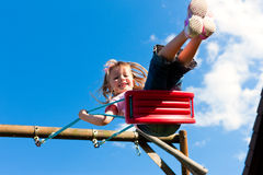Girl child on swing in the garden Royalty Free Stock Images