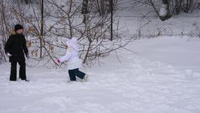 Girl child and teenager boy playing snowballs. Children  in winter park. stock footage