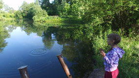 Girl child throwing small stones in water of pond . The pond is located in the old overgrown park. Blue sky and trees reflected in the surface of the water stock video footage