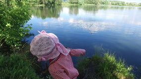 Girl child throws a stick into water of pond . The pond is located in the old overgrown park. stock video footage