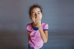 The girl child is tired closes her mouth yawns on Stock Image