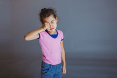 The girl child is tired rubs his eyes on gray Royalty Free Stock Photo
