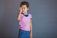 The girl  child  is tired rubs his eyes on gray Royalty Free Stock Photography
