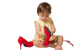 Girl-child trying on  mother's big red shoes Stock Photo