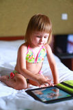 The girl child is using the tablet work game cartoon self swimsuit Stock Photos