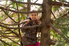 Girl child walking in park hiding among tree branches Stock Photo