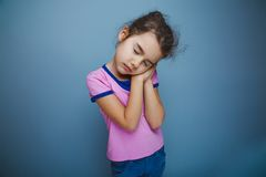 Girl child wants to sleep hands under her cheek on Stock Photos