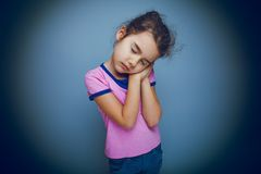 Girl child wants to sleep hands under her cheek on Royalty Free Stock Images
