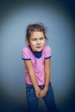 Girl child wants to use the toilet on a gray Stock Photography