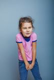 Girl child wants to use the toilet on a gray Royalty Free Stock Image