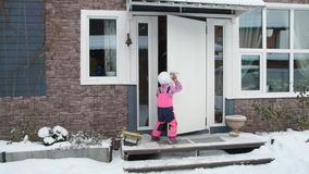 Girl, child winter opens the door, goes in house. The girl, child winter opens the door, goes in house stock footage