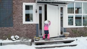 Girl, child winter opens the door, goes in house. The girl, child winter opens the door, goes in house stock video footage