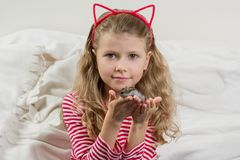 Girl child 7 years old blonde with long wavy hair holds in the hands of her beloved pet - hamster. Royalty Free Stock Images