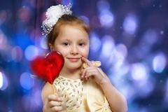 Girl child in a yellow dress with a white bow holding a lollipop royalty free stock images