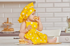 Girl the child in a yellow suit of the cook stock image