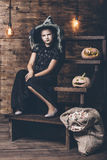 Girl childl in witch costume with pumpkins and candy at the Hall Royalty Free Stock Image