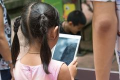 A Girl children playing tablet and don`t care anything. stock photography