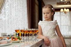 The girl on a children's buffet table. At the table with drinks and food Royalty Free Stock Images