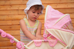Girl with children's carriage Stock Photos