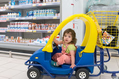 Girl in a children's machine in a supermarket Royalty Free Stock Photography