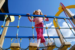 The girl on a children's playground. The girl in the summer against the sky on a playground goes on the bridge Royalty Free Stock Photos