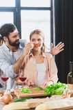 Girl with chili pepper as mustache. Young people having fun together, blonde girl with chili pepper as mustache royalty free stock photos
