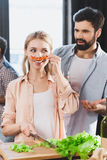 Girl with chili pepper as mustache. Young people having fun together, blonde girl with chili pepper as mustache stock images