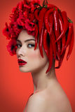 Girl with chilli peppers and flowers Royalty Free Stock Photography