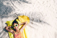 Girl chilling on tropical island. Child girl in yellow swimwear and sunglasses chilling on lilo under palm tree on sand at the beach. Tropical island. Summer Royalty Free Stock Photos