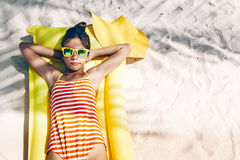 Girl chilling on tropical island. Child girl in yellow swimwear and sunglasses chilling on lilo under palm tree on sand at the beach. Tropical island. Summer Stock Photo