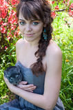 Girl with chinchilla. Pretty young woman model with bright colorful makeup wearing summer dress, blue earrings, holding her pet chinchilla on her hands, looking Stock Image