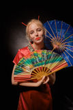 Girl in chinese costume. With fan and umbrella on black background Royalty Free Stock Photo