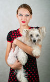 Girl and chinese crested dog. The beautiful girl and chinese crested dog on grey background. Shallow DOF royalty free stock image