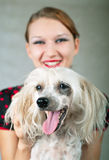 Girl and chinese crested dog on grey. The beautiful girl and chinese crested dog on grey background. Shallow DOF, focus on dog stock photos