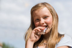 The girl with chocolate. Rejoices to a sunny day on summer vacations Stock Photos