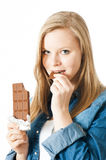 Girl with chocolate. Girl biting a bar of chocolate royalty free stock images