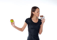 Girl with chocolate and apple in  hands Stock Images