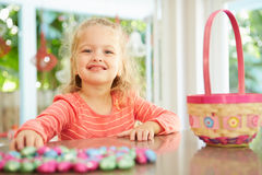 Girl With Chocolate Easter Eggs And Basket At Home Stock Photos