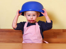 Girl with chocolate mouth holding the mixing bowl over her head. After licking the mixing bowl girl is holding the mixing bowl on her head; she has a cute Stock Photography