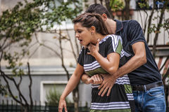 Girl is choking. Guy helping a girl while choking Stock Photography