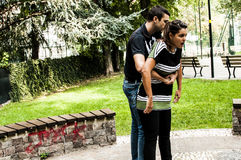 Girl is choking. Guy helping a girl while choking stock images