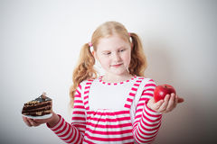 Girl choose from  cake and red apple Stock Photos