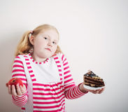 Girl choose from sweet cake and apple Royalty Free Stock Image