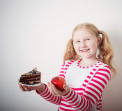 Girl choose from sweet cake and apple Royalty Free Stock Photography