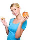 Girl choose from sweet cake and fresh apple Royalty Free Stock Photos