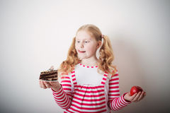 Girl choose from sweet cake and red apple Stock Image