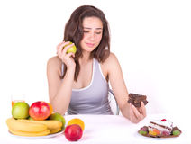 Girl chooses between an apple and a cake Stock Photography