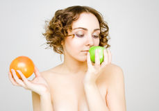 Girl chooses between an apple or grapefruit Royalty Free Stock Photography