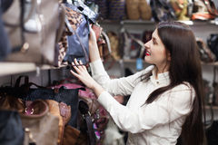 Girl chooses bag at shop Stock Images